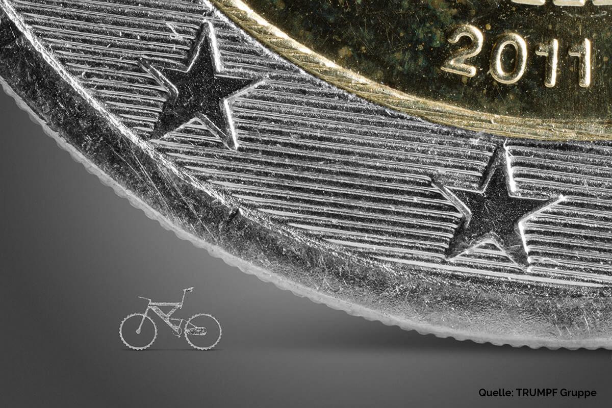 Mikroschneiden: Filigranes Fahrrad neben Euromünze